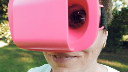 Female eye through VR glasses lens. Huge terrific and fun eye movement through magnifying glass. Funny and absurd image. Playing fool game concept.