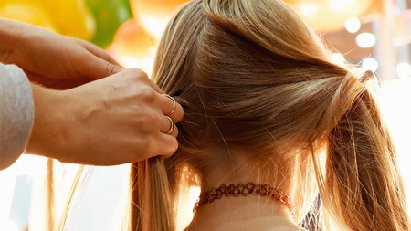 important event: Female model getting her hair dressed before an event. Makeup appearance and hairstyle are important for every beautiful woman. Stock Photo