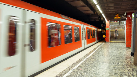 arrives: Hamburg, Germany - October, 10, 2016: Metro subway train arrives to station. People at subway metro underground tube station walk to get the arriving train. European public transportation system. Editorial