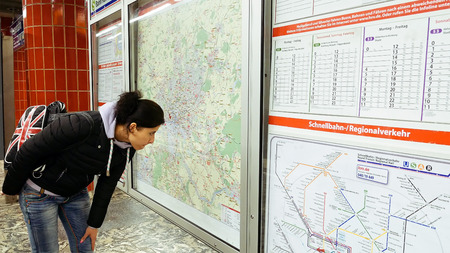 Hamburg, Germany - October, 10, 2016: Young woman looking at subway metro underground tube map on train station. Tourist use public transportation subway metro system in a big European city. Editorial
