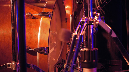 soft pedal: Drummer plays on a bass drum set with pedal on the stage. Jazz or rock concert performance entertainment. Close up shot with soft selective focus.