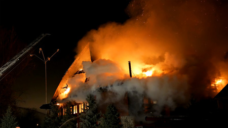 extinguishing: House building on fire at night. Inferno conflagration.