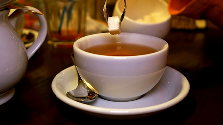 Adding sweet lump sugar with pincers tweezers to black tea cup. Tea time lunch snack breakfast dinner and supper relax concept.