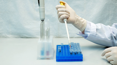 Lab technician scientist performs medical clinic chemical analysis and diagnostics using test tube phial and pipette. Stock Photo