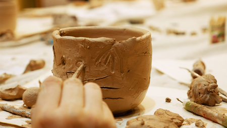 Child ceramist sculptor is modeling clay pot or ceramics vase bowl. Art and handicraft modelling creation.