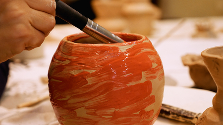 Art ceramist sculptor is painting clay pot or ceramics vase bowl to finish it. Art and handicraft modeling creation. Stock Photo