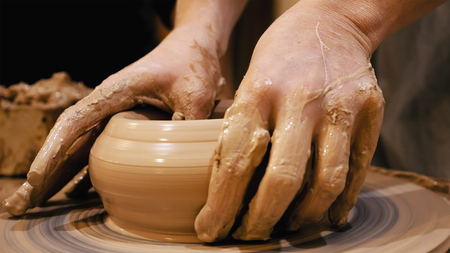 Potter is making clay pot bowl or vase ceramics porcelain on the potters wheel. Creating pottery art and handicraft modelling creation. Stock Photo