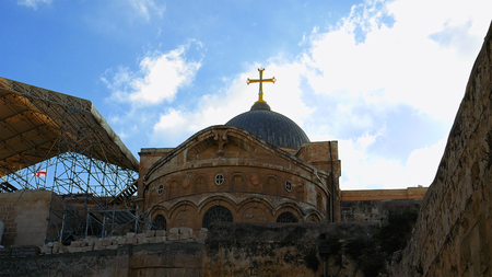 Golden cross over Temple of the Holy Sepulcher church in Jerusalem. The Holy Sepulchre Church is the most sacred place for all Christians in the world. Stock Photo