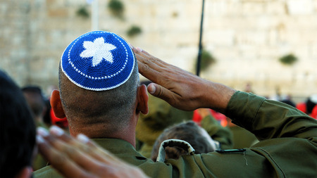 Jerusalem, Israel - May 25, 2017: Israeli soldier military man saluting to the Western wall in Jerusalem. Western wall or Wailing wall or Kotel is the most sacred place for all jewish people.