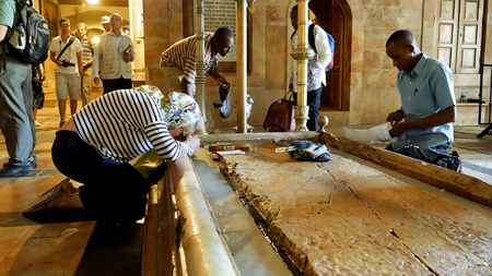 Jerusalem, Israel - May 25, 2017: Prayers at the Stone of Anointing in the Holy Sepulcher Church in Jerusalem. The Church and Empty Tomb the most sacred places for all Christians people in the world. Editorial