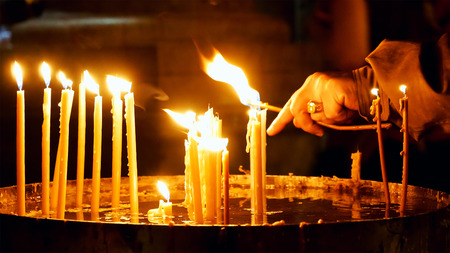 Burning candles in the Holy Sepulcher Church in Jerusalem. The Holy Sepulchre Church and Empty Tomb the most sacred places for all religious Christians in the world. Stock Photo