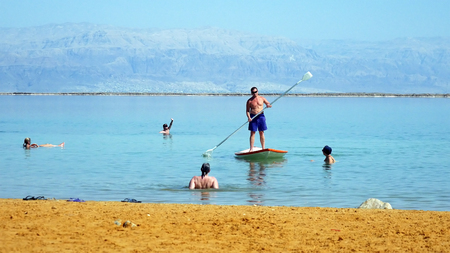 Dead Sea, Israel - May 22, 2017: Stand up paddle boarder on the Dead Sea. Lifeguard uses the paddle boards at the Dead sea beaches to fast and safe movement in water.