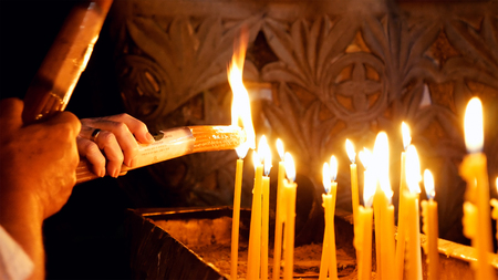 Jerusalem, Israel - May 25, 2017: Prayers lighting candles in the Holy Sepulcher Church in Jerusalem. The Holy Sepulchre Church and Empty Tomb the most sacred places for all Christians in the world. Editorial