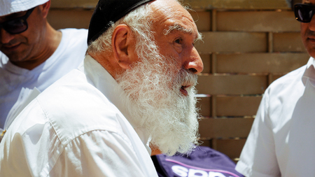 kippah: Jerusalem, Israel - May 25, 2017: Jewish senior old man with beard talks with emotions and expression to another man outdoors. All jews are used to wear the kippah or yarmulke small hat.