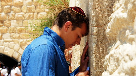 jewish: Jerusalem, Israel - May 25, 2017: Jewish man pray at the Western Wall also known as Wailing Wall or Kotel in Jerusalem. The Western Wall is the most sacred place for all jews and jewish in the world.