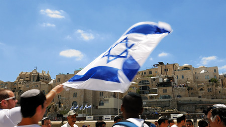 Jerusalem, Israel - May 25, 2017: Jews dancing in a round with flag celebrating the Jerusalem Day at Western Wall - Wailing Wall or Kotel - the most sacred place for all jews and jewish in the world. Editorial