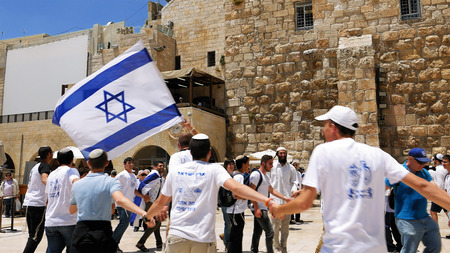 jewish: Jerusalem, Israel - May 25, 2017: Jews dancing in a round with flag celebrating the Jerusalem Day at Western Wall - Wailing Wall or Kotel - the most sacred place for all jews and jewish in the world. Editorial