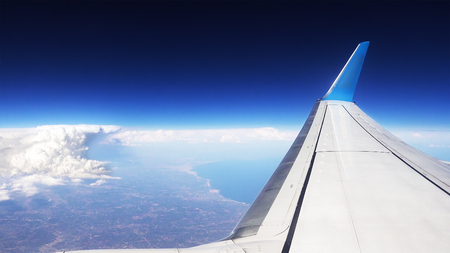 Flying over the clouds. View from plane aircraft passenger window. Clouds and skyline horizon panoramic view. Stock Photo