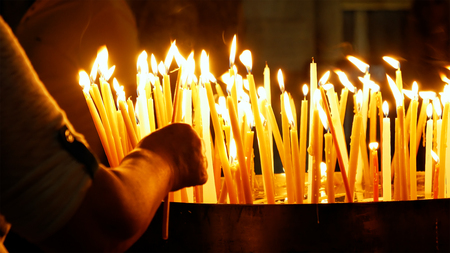 Burning candles in the Holy Sepulcher Church in Jerusalem. The Holy Sepulchre Church and Empty Tomb are the most sacred places for all religious Christians in the world.