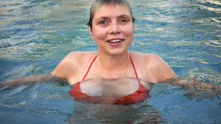 Young woman in red bikini is emerging from the water in swimming pool. Diving and coming up is good time sport recreational enjoyment in a water pool.