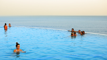 estate: Sharm-El-Sheikh, Egypt - August 27, 2017: People are swimming in the infinity pool at the tropical sea resort at sunset. Infinity pool is an attribute of luxury resort or property estate. Editorial