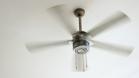 Ceiling fan is rotating at the ceiling of the room. Electric climate equipment. 版權商用圖片