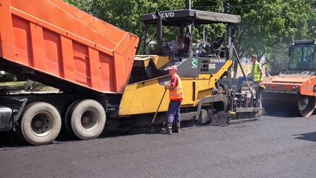 Kiev, Ukraine - June 19, 2017: Road construction. Applying new hot asphalt using road construction machinery and power industrial tools. Roadworks repaving process.