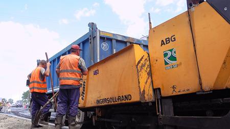 Kiev, Ukraine - June 19, 2017: Road construction. Workers applying new hot asphalt using road construction machinery and power industrial tools. Roadworks repaving process.