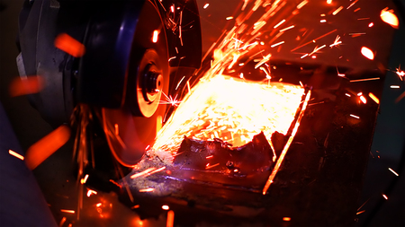 Cutting metal with disc grinder abrasive saw producing bright colorful sparks. Worker cuts metal with hand electric tool.