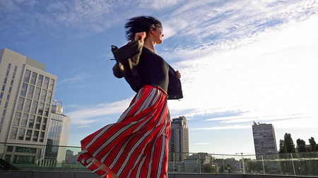 Beautiful brunette woman is dancing feeling happy outdoors. City life urban young happy people behavior. Sunset cityscape clear sky shot. The woman wears long striped pleated skirt.