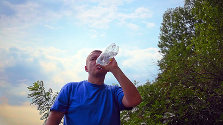 Handsome man is drinking fresh water from a plastic bottle. Recreational activity outdoors . Sunset shot. Stock Photo