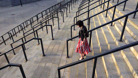 Beautiful brunette woman in red striped pleated skirt is running downstairs. City life urban people behavior. The skirt and her hair are fluttering in the wind. High angle overhead.