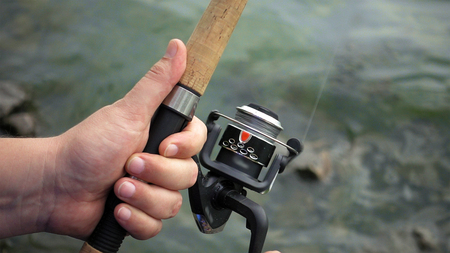 Fishing reel closeup. Man is fishing with spinning fishing rod close to coast shore line. Outdoor recreational activity.