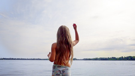 Little cute blond longhair girl is standing at riverside bank coast. Family recreational activity outdoors. Sunset shot.