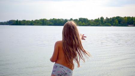 Little cute blond longhair girl is standing at riverside bank coast. Family recreational activity outdoors. Sunset shot.
