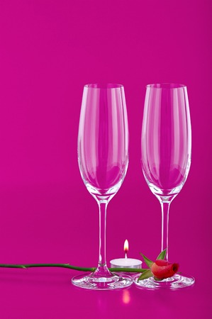 Two wine glasses with rose and candle on pink background
