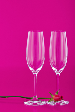 Two wine glasses with rose flower on pink background