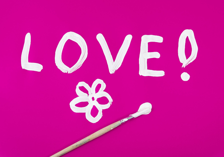 Love word with flower painted on pink background