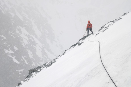 A Mountain climber with rope on the slope. Ascent on Metallurg Peak. Altai Republic, Russia