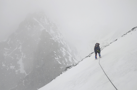 A girl mountain climber with rope on the slope. Ascent on Metallurg Peak. Altai Republic, Russia