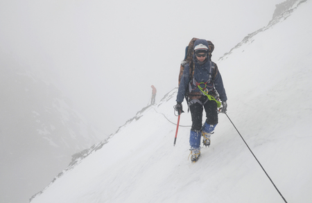 A two mountain climbers, girl and man, with rope on the slope. Ascent on Metallurg Peak. Altai Republic, Russia