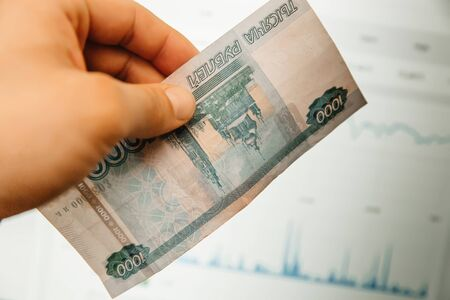 A hand holds Russian banknotes against the background of trading charts. The concept of exchange rates Imagens