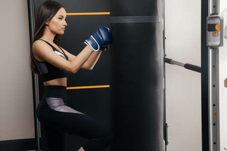 Beautiful tanned 30-year-old woman hits a punching bag. The concept of self-defense and protection Foto de archivo