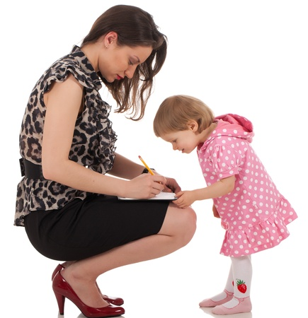 pencil skirt: Business lady is writing something into organizer book and her daughter is checking and trying to find when mom is available for playing with her Stock Photo