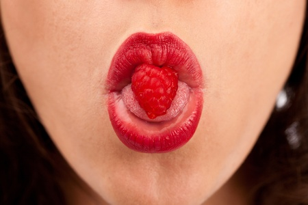 Fresh and attractive raspberry with a shape of the heart in a womens mouth