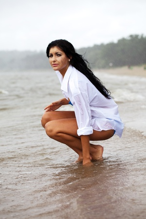 long black hair: Lonely girl cries in the rain on the empty beach.