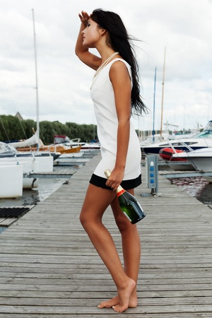 Young lady is waiting for her sailor man with a bottle of sparkling wine Stock Photo
