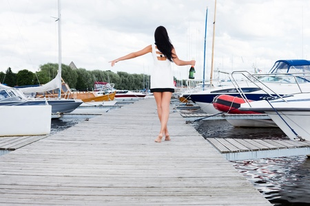 Young lady is looking for a boat taking her in. Stock Photo