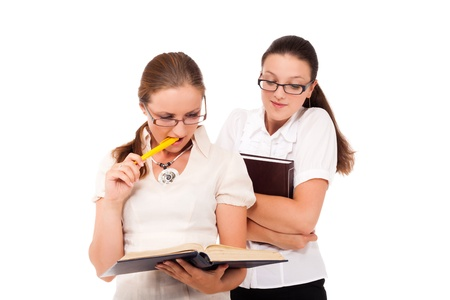Two student girls are reading the same book. Stock Photo - 10893490
