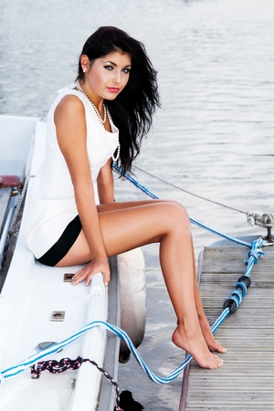 Young lady is waiting for her sailor man sitting on the boat